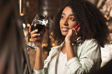 Inviting to drink. Beautiful young woman sitting at the bar, drinking wine and having a phone conversation with her friend, inviting her to have a drink together - 213573862