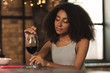 Relaxing pastime. Charming young woman running a finger along a rim of glass of a red wine while sitting at the bar counter