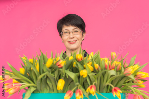 Portrait of beautiful middle-aged woman with yellow tulips on pink background. Floristics, holidays and gifts concept - 213575244