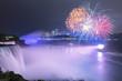 Niagara Falls lit at night by colorful lights with fireworks, Niagara Falls, NY, USA
