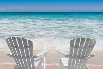 Beach chairs on sandy beach and turquoise sea. Summer vacation and travel concept.