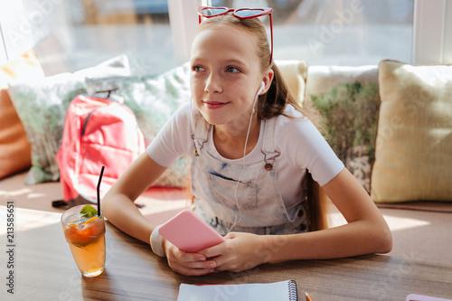 Listening to music. Modern appealing schoolgirl feeling relaxed while listening to music using earphones - 213585651
