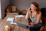 Happy woman. Red-haired beaming woman feeling extremely happy while calling her husband - 213587214
