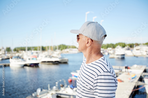 Leinwanddruck Bild Pensive dreamy mature man in cap and sunglasses being on vacation looking at sailboats while standing on pier in yacht club