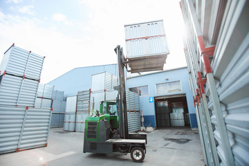 Modern powerful forklift truck lifting metal container while stacking it on others in outdoor storage area