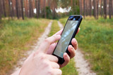 Young woman holding a smartphone and looking for a route in a navigation application, on a forest