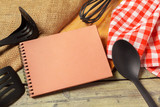 Blank sheet of opened notepad and kitchen utensils on  table with tablecloth, copy space - 213591234