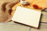 Blank sheet of opened notepad and kitchen utensils on  table with tablecloth, copy space - 213591249