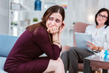 Crying person. Unhappy young woman turning her head and trying not to cry while visiting a professional psychologist - 213596452