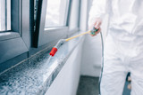 cropped image of pest control worker spraying pesticides on windowsill at home - 213598226