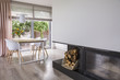 Leinwanddruck Bild - Fireplace next to white chairs at table in bright dining room interior with window. Real photo