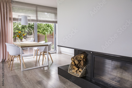 Leinwanddruck Bild Fireplace next to white chairs at table in bright dining room interior with window. Real photo