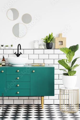 Zielony szafka obok zakładu na stole złota w nowoczesnym wnętrzu łazienki z lustrami. Prawdziwe zdjęcie