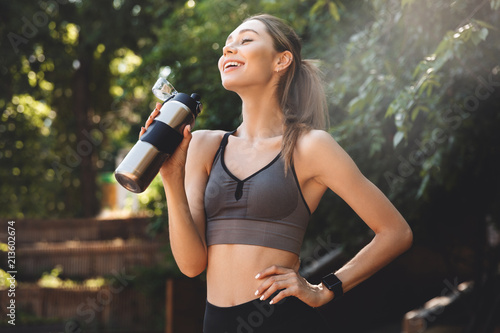 Leinwanddruck Bild Cheerful young fitness girl drinking water