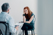 Scared young woman talking to a therapist about abuse in a bright office