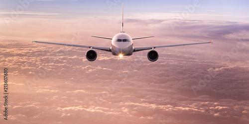 Leinwandbild Motiv Commercial airplane flying above dramatic clouds during sunset.