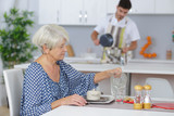 cheerful young man serving breakfast to an elderly woman - 213611650