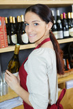 pretty young woman examining the bottle of white wine - 213615211