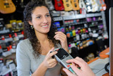 Shop assistant taking card payment from customer - 213616065