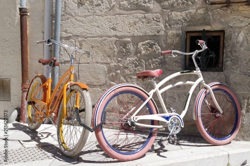Aluminium Fiets Two retro bicycles parked against a stone wall in a medieval village. This mean of transport became a symbol for the ecologists.