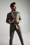 portrait of elegant man buttoning his green suit - 213628693