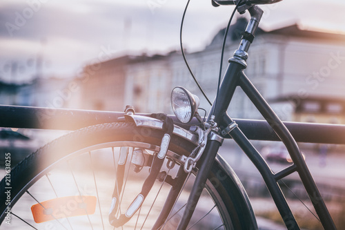 Foto Spatwand Fiets Detail of a black retro bicycle on a city background, image with vintage toning