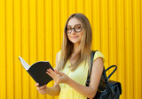 Pretty smiley girl student with book wearing funny toy round glasses and suitcase - 213642208