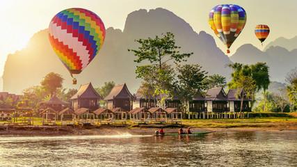 Hot air balloon over Nam Song river at sunset in Vang vieng, Laos. © tawatchai1990