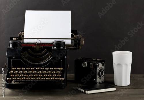 Foto Murales Vintage typewriter with empty, blank sheet of paper, camera, cup and notebook on wood table