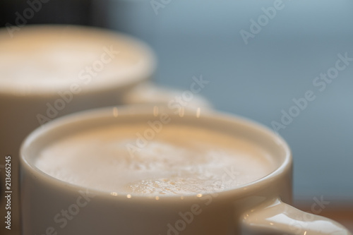 Close up of mug cup of hot coffee latte with milk foam.