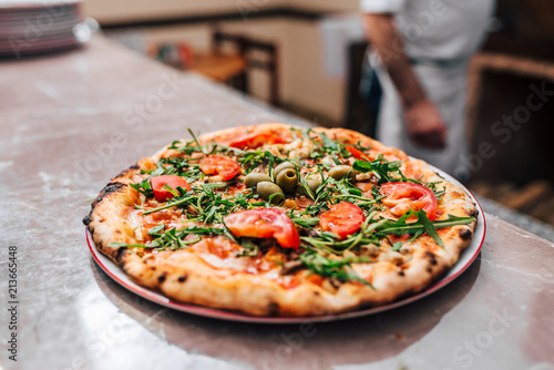 Delicious pizza on the plate. Chef in the background. - 213665448