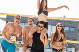 Outdoors portrait of happy guys and girls on vacation standing near volleyball net, celebrating game won, boyfriend piggybacking his girlfriend being overjoyed with victory on the beach