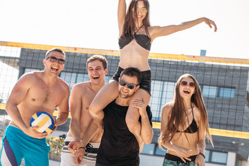 Outdoors portrait of happy guys and girls on vacation standing near volleyball net, celebrating game won, boyfriend piggybacking his girlfriend being overjoyed with victory on the beach © alfa27