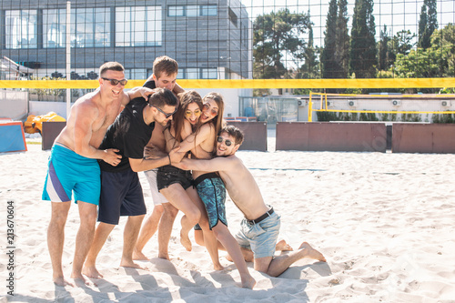 Happy caucasian guys and chicks being in carefree, relaxing mood having fun on hotel volleyball court on a sunny morning