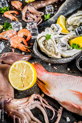Fototapeta Fresh raw seafood squid shrimp oyster mussels fish with spices of herbs lemon on dark rusty background copy space top view