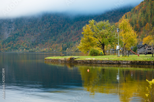 Fotobehang Herfst Beautiful autumn view of calm Hallstatt lake, mountains with fog and village. Beautiful countryside in autumn. Austria