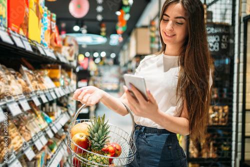 Leinwanddruck Bild Female customer uses mobile phone in supermarket