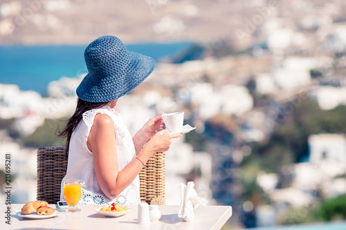 Fototapeta Woman having breakfast at outdoor cafe with amazing view on Mykonos town.