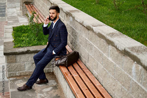 Poster Man wearing suit chatting on phone on the street.