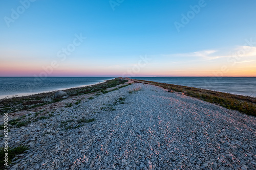 Fotobehang Blauw dramatic sunrise over the baltic sea with rocky beach and trees on the shore
