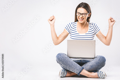 Business concept. Portrait of happy woman in casual sitting on floor in lotus pose and holding laptop isolated over white background.