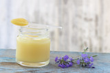 organic royal jelly in a glass bottle and full spoon on , with lavender decoration - 213716492