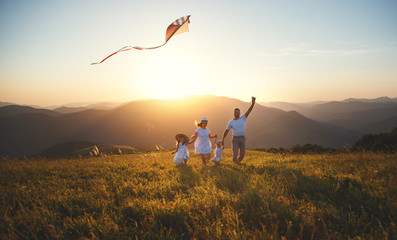 Happy family father,  mother and children launch  kite on nature at sunset © JenkoAtaman