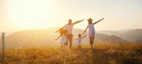 Leinwandbild Motiv Happy family: mother, father, children son and daughter on sunset