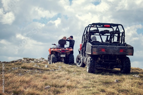 Friends driving off-road with quad bike or ATV and UTV vehicles