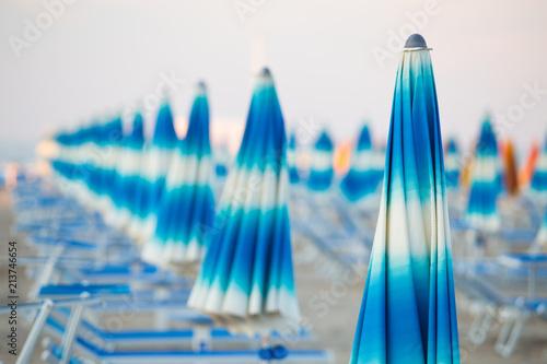 Foto Murales Blue sun umbrellas standing in a row