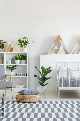 Fototapeta Patterned carpet on the floor in real photo of bright bedroom interior for teenager with fresh plants, metal bed and mountain shape decor