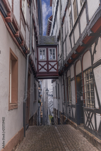 Aluminium Smalle straatjes narrow paved cobblestone street steeply going down in the old part of the German city of Marburg