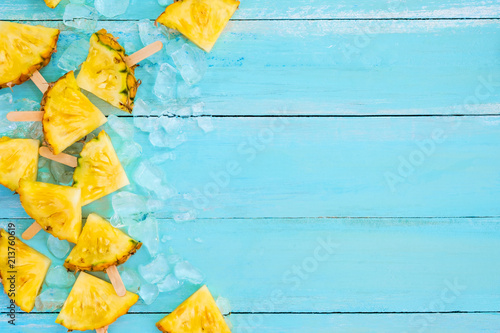 Pineapple popsicle sticks with ice on wood plank blue color. summer fruit backgrond concept, top view, copy space