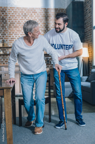 Leinwanddruck Bild Heart of gold. Attractive content bearded man smiling and helping an old man while he walking with his stick